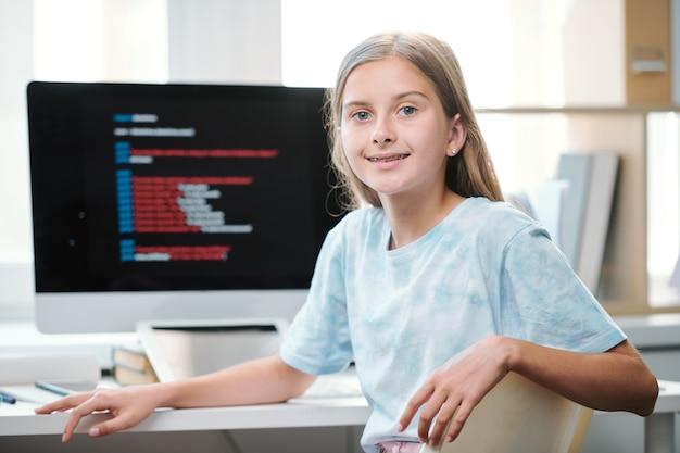 Aantrekkelijke middelbare schoolstudent in vrijetijdskleding op zoek naar jou zittend door een bureau voor computermonitor