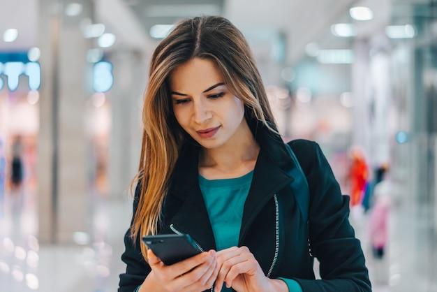 Aantrekkelijke modeblogger die door een wandelgalerij loopt met mobiele telefoon in handen