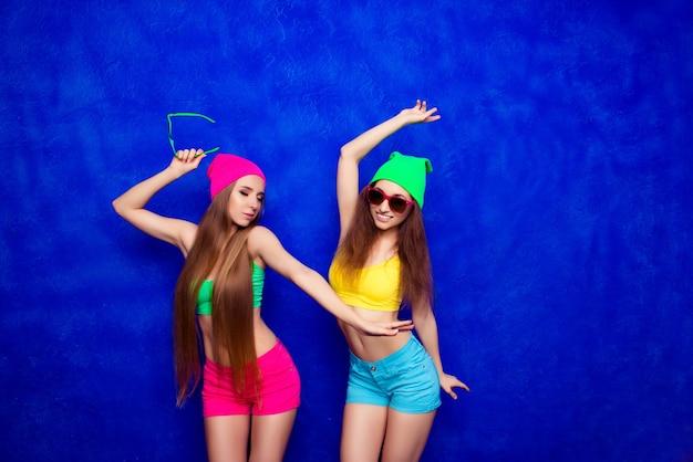 Aantrekkelijke moderne gelukkige meisjes dansen op blauw