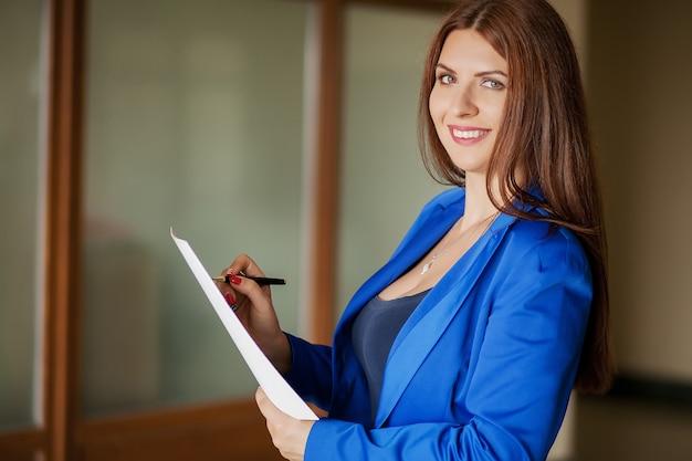 Aantrekkelijke moderne jonge bedrijfsvrouw in bureau