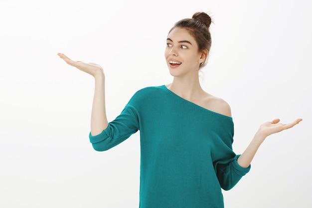 Aantrekkelijke moderne vrouw die een beslissing neemt, keuzes afwegen, de linkerhand opheft met het product of uw logo