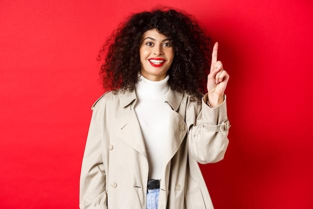 Aantrekkelijke moderne vrouw met rode lippen, krullend kapsel, lente-trenchcoat, wijzende vinger omhoog en glimlachen, staande tegen rode achtergrond.