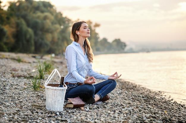 Aantrekkelijke modieuze blanke jonge vrouw zittend op kust in de buurt van rivier, muziek luisteren en mediteren. naast haar staat een picknickmand.