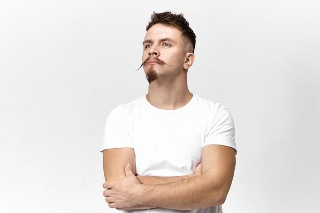 Aantrekkelijke modieuze jonge bebaarde europese hipster in wit t-shirt die de armen kruist en omhoog kijkt, beledigd of beledigd is, zeg geen woorden, wachtend op uw excuses. portret van trotse hooghartige man