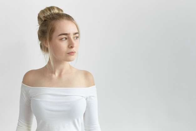 Aantrekkelijke modieuze jonge blanke vrouw, gekleed in witte top met open schouders met diep in gedachten peinzende blik, geïsoleerd poseren