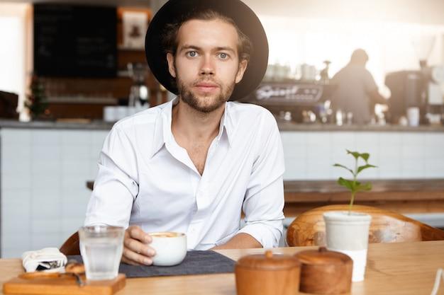 Aantrekkelijke modieuze jonge man met baard met koffie in modern café