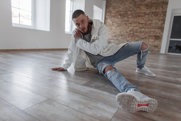 Aantrekkelijke modieuze jonge model man met een baard in een stijlvolle jas en mode gescheurde spijkerbroek met sneakers zit op de houten vloer
