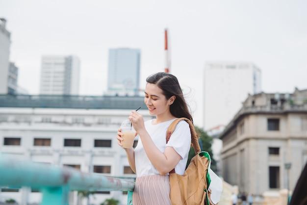 Aantrekkelijke modieuze schattig meisje buiten koffie drinken.