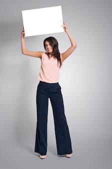 Aantrekkelijke modieuze vrouw met whiteboard boven haar hoofd