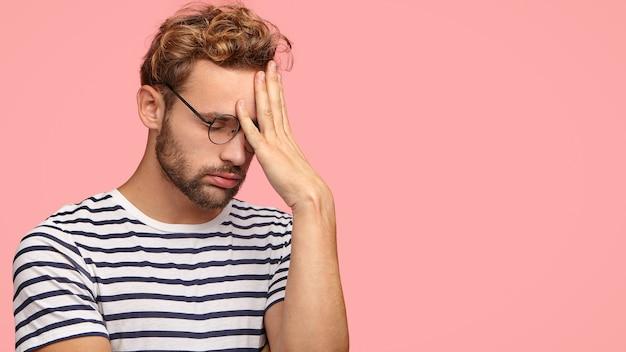 Aantrekkelijke moe overwerkte man ondernemer zucht van vermoeidheid, houdt de hand op het voorhoofd, lijdt aan hoofdpijn