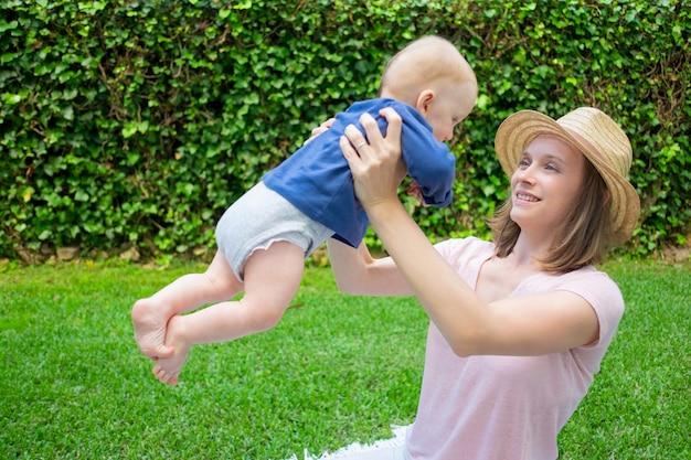 Aantrekkelijke moeder in hoed spelen met pasgeboren, glimlachen en kijken naar hem. kleine roodharige baby in blauw shirt op moederhanden