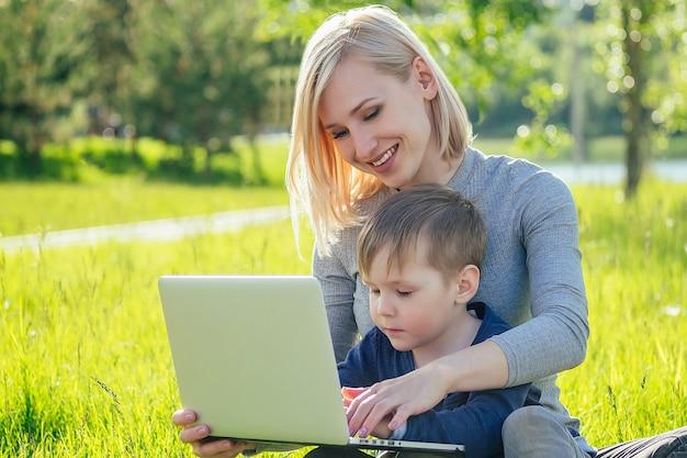 Aantrekkelijke moeder vrouwelijke persoon en kleine jongen kijken tekenfilms op een laptop in het park op een achtergrond van groen gras en bomen.