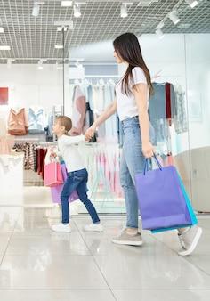 Aantrekkelijke moeder winkelen met dochtertje in winkelcentrum