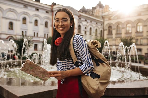 Aantrekkelijke mooie aziatische brunette vrouw i zijden rok, gestreept shirt en bril kijkt naar voren, glimlacht
