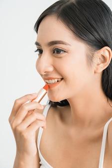 Aantrekkelijke mooie gemengde ras aziatische vrouw die lippenstift op haar lippen over witte muur toepast