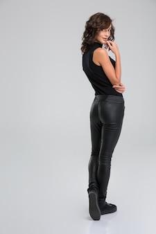 Aantrekkelijke mooie mooie speelse jonge vrouw in zwarte broek en top poseren op witte muur