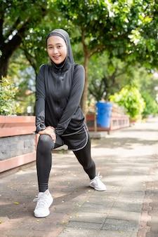 Aantrekkelijke moslim aziatische vrouw strecth haar been tijdens sport buiten in zonnige dag