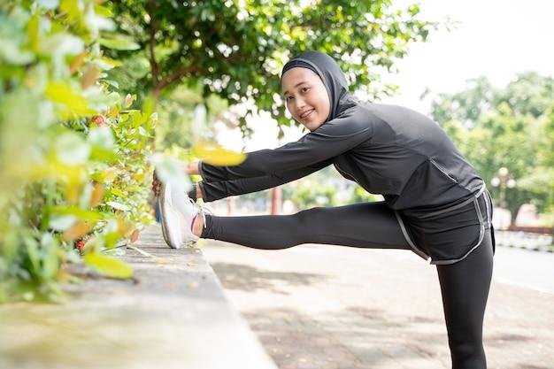 Aantrekkelijke moslim aziatische vrouw strekt haar been uit tijdens sporttijd buiten op zonnige dag