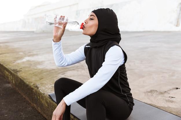 Aantrekkelijke moslim sportvrouw die hijab buitenshuis draagt, zittend op een fitnessmat, drinkwater