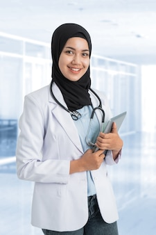 Aantrekkelijke moslim vrouwelijke arts met witte jas glimlachen
