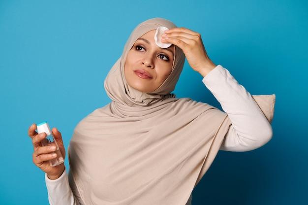 Aantrekkelijke moslimvrouw make-up verwijderen uit haar gezicht met micellair water en wattenschijfje.