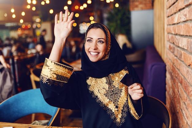 Aantrekkelijke moslimvrouw met brede glimlach die kelner roept om haar in rekening te brengen. cafetaria interieur.
