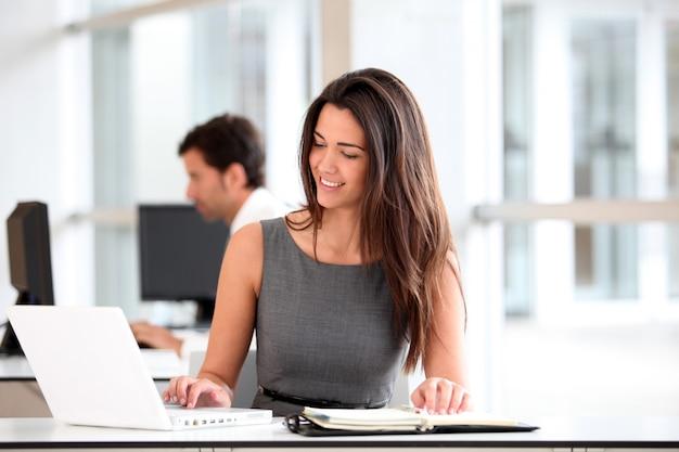 Aantrekkelijke onderneemster die aan laptop computer werkt