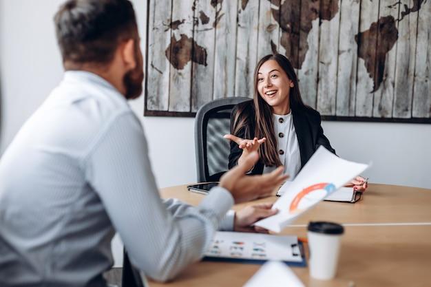 Aantrekkelijke onderneemster die in bedrijfsbureau actief project bespreekt met haar collega