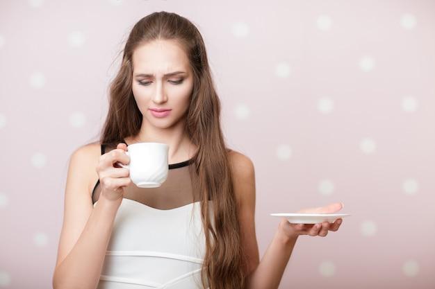 Aantrekkelijke ongelukkige vrouw met witte kop met koffie op roze achtergrond