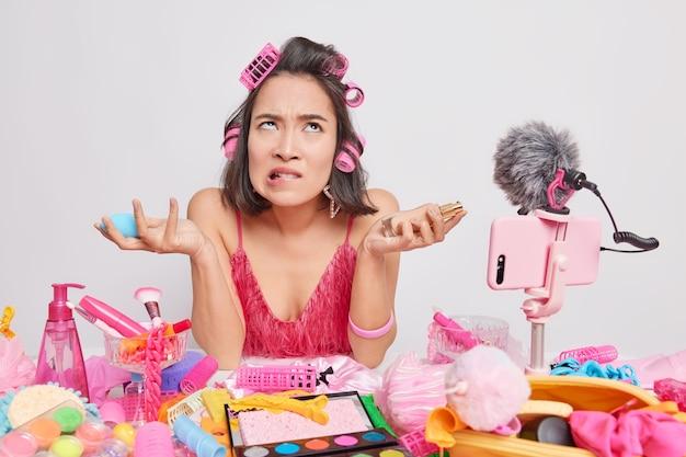 Aantrekkelijke ontevreden jonge aziatische vrouw die het zat is om make-upgesprekken te voeren over cosmetische producten