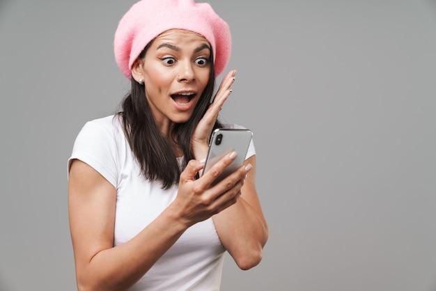 Aantrekkelijke opgewonden, gelukkige jonge brunette vrouw met een baret die geïsoleerd staat over een grijze muur en mobiele telefoon vasthoudt