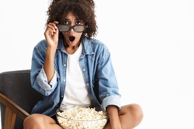 Aantrekkelijke opgewonden jonge vrouw met denim in een stoel geïsoleerd over een witte muur, een film kijkend, popcorn etend