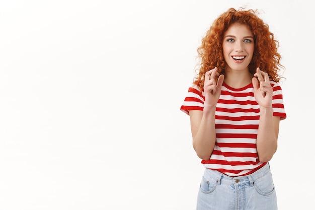 Aantrekkelijke optimistische vrolijke lachende roodharige krullende vrouw blauwe ogen kruis vingers veel geluk grijnzend hopelijk anticiperen op goed nieuws staande witte muur