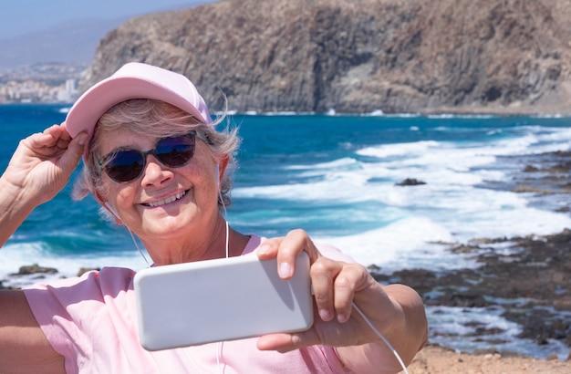 Aantrekkelijke oudere vrouw met mobiele telefoon die selfie op zee neemt in winderige dag. senior mensen genieten van vakantie en schoonheid in de natuur, bergen, strand en golven op de achtergrond