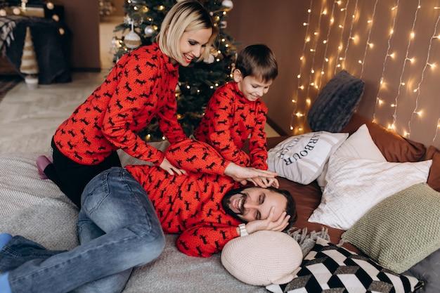 Aantrekkelijke ouders en hun zoontje in rode truien hebben plezier vóór het kerstfeest op het bed liggen