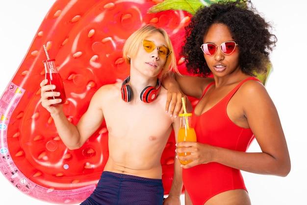 Aantrekkelijke paar europese jongen en afrikaans meisje in zwemkleding met zonnebril en koptelefoon met cocktails in hun handen