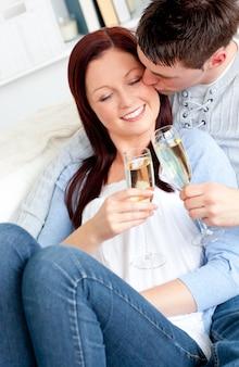 Aantrekkelijke paar het drinken champagne die op de bank ligt