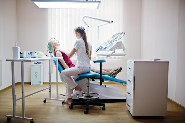 Aantrekkelijke patiënt die in rood-violette kleding op de tandstoel legt terwijl vrouwelijke tandarts haar tanden behandelt met speciale instrumenten.