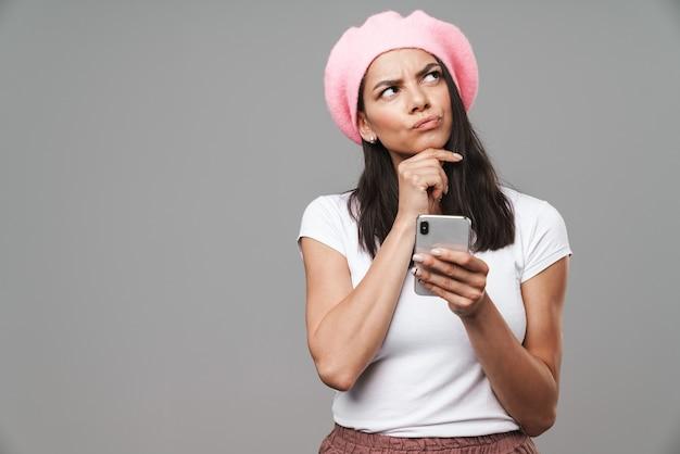 Aantrekkelijke peinzende jonge donkerbruine vrouw die baret draagt die zich geïsoleerd over grijze muur bevindt, die mobiele telefoon houdt