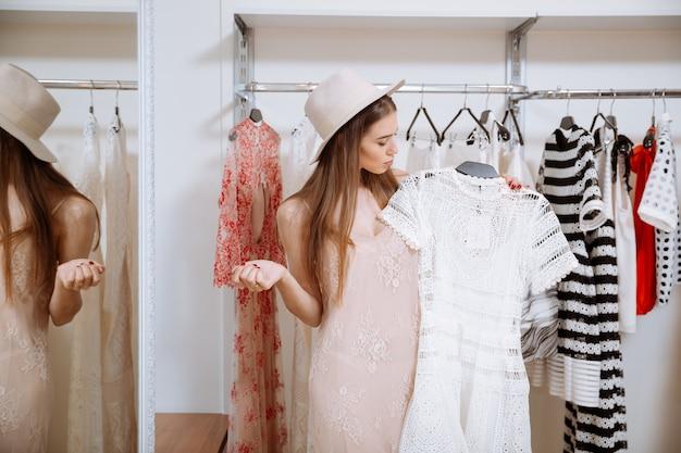 Aantrekkelijke peinzende jonge vrouw permanent en kleding in kledingwinkel kiezen