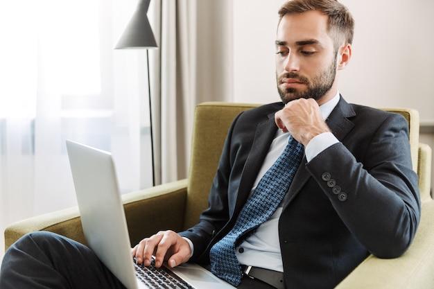Aantrekkelijke peinzende jonge zakenman in een pak zittend in een stoel in de hotelkamer, werkend op laptopcomputer