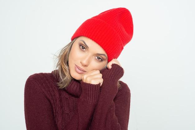 Aantrekkelijke peinzende vrouw in rode hoed