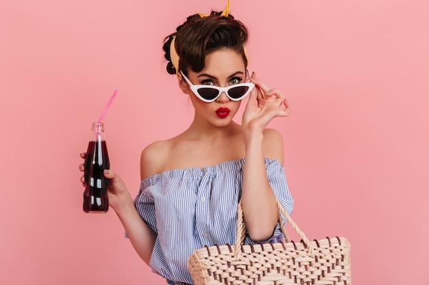 Aantrekkelijke pinup vrouw frisdrank drinken. charmante brunette meisje in gestreepte blouse zonnebril op roze achtergrond aan te raken.