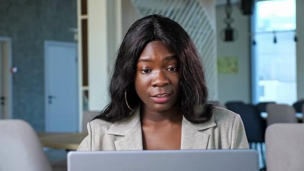 Aantrekkelijke positieve afro-amerikaanse vrouw praat over videochat via moderne laptop aan tafel in een gezellig restaurant van dichtbij bekeken
