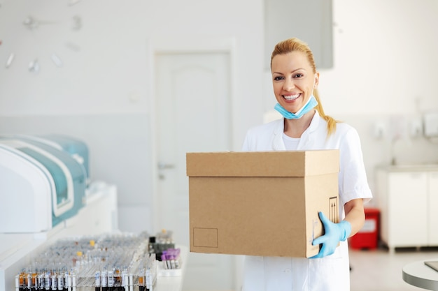 Aantrekkelijke positieve blonde laboratoriumassistent met doos met vaccins voor covid 19. laboratoriuminterieur.
