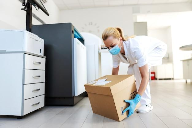 Aantrekkelijke positieve blonde laboratoriumassistent met doos met vaccins voor covid 19.