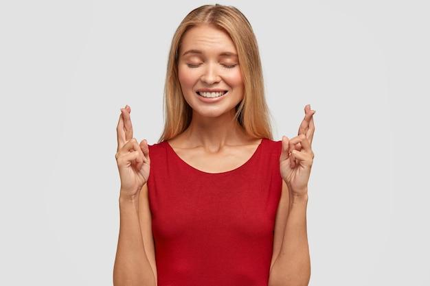 Aantrekkelijke positieve blonde vrouw wil rijbewijs halen, kruist vingers, doet wensen, hoopt dat dromen uitkomen