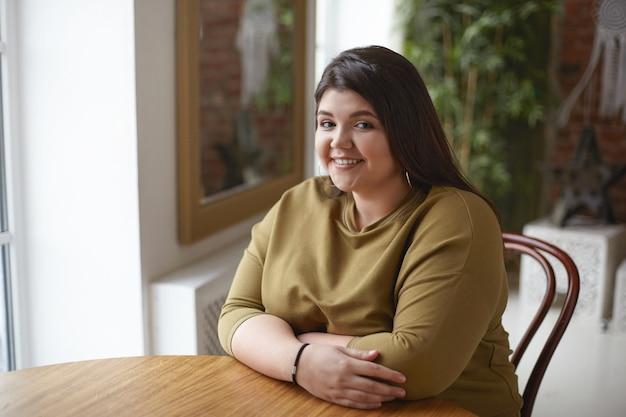 Aantrekkelijke positieve brunette meisje met largy bochtige lichaam zit alleen aan café tafel, wachtend op haar lunch. foto van mooie plus size jonge vrouw poseren in een stijlvol, gezellig interieur, gelukkig lachend