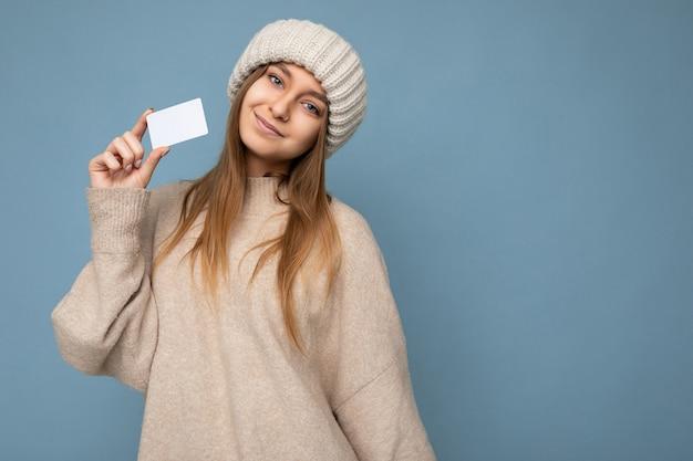 Aantrekkelijke positieve glimlachende jonge donkerblonde vrouw die beige trui en gebreide beige hoed draagt, geïsoleerd over blauwe achtergrond die creditcard vasthoudt en naar de camera kijkt