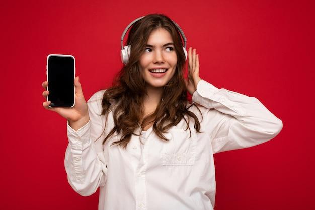 Aantrekkelijke positieve glimlachende jonge vrouw, gekleed in stijlvolle casual outfit geïsoleerd op kleurrijk